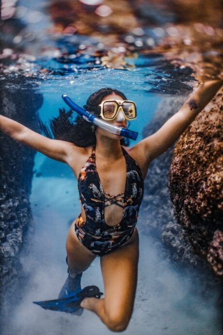 woman in blue and white floral swimsuit wearing white goggles